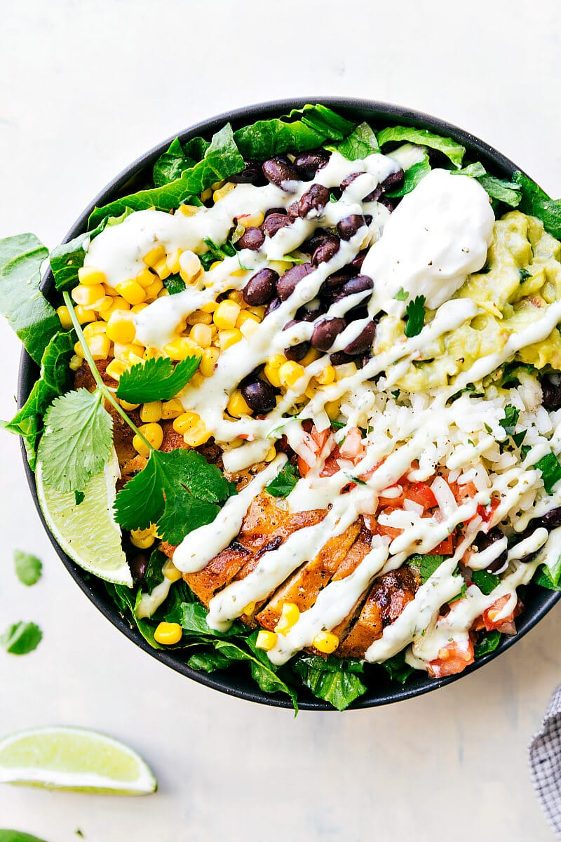 PINSPIRATION : Mouthwatering Healthy Buddha Bowl Recipes That You Must Introduce Into Your Weekly Menu | Chicken Burrito Bowls made with taco-seasoned chicken, cilantro-lime rice, salsa, guacamole, corn, beans, and a delicious creamy cilantro sauce.